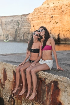 Photo of Girls Sitting Near the Cliff