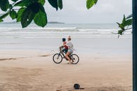 Man in White Shirt Riding Bicycle on Beach