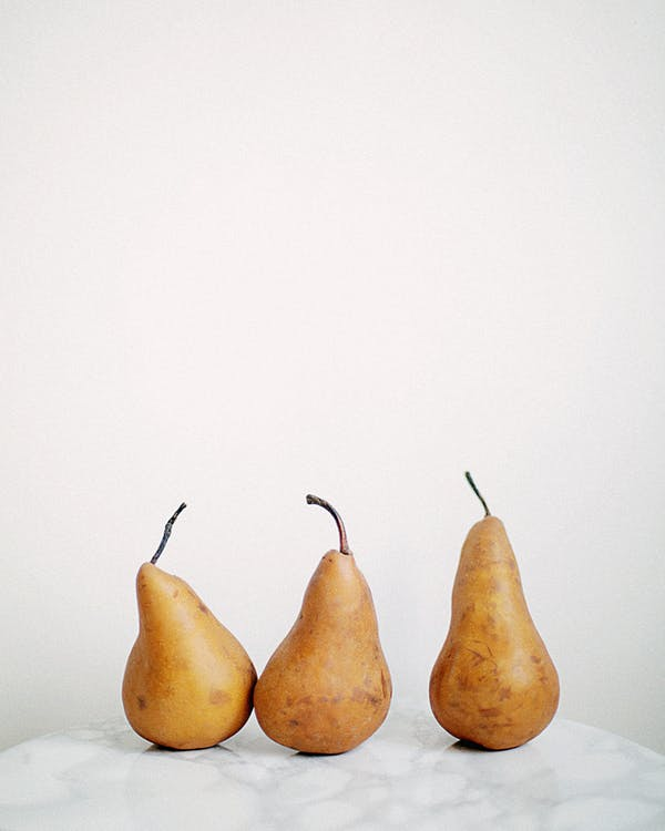 Three Brown Fruits on White Textile