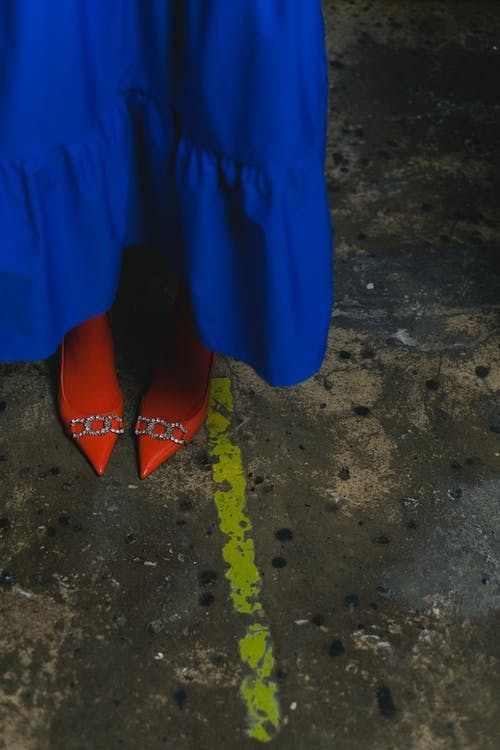 A Person in a Blue Dress and Red Shoes