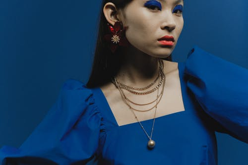 Woman in Blue Dress Wearing Gold Necklace