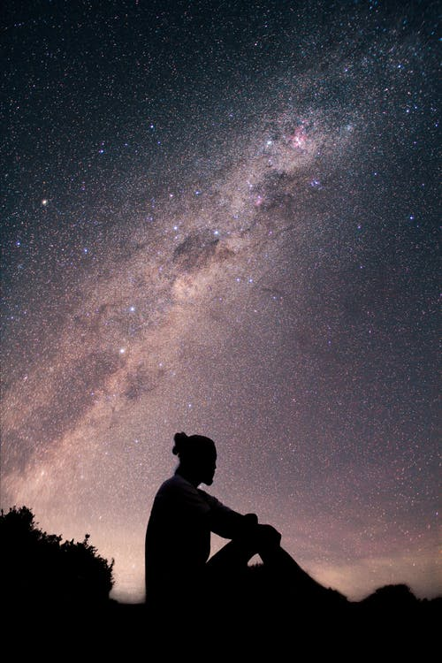 Silhouette of Man Standing Under Starry Night