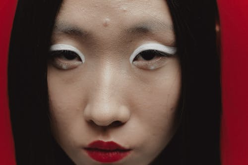 Close-Up Photo of Woman with White Eyeshadow and Red Lips