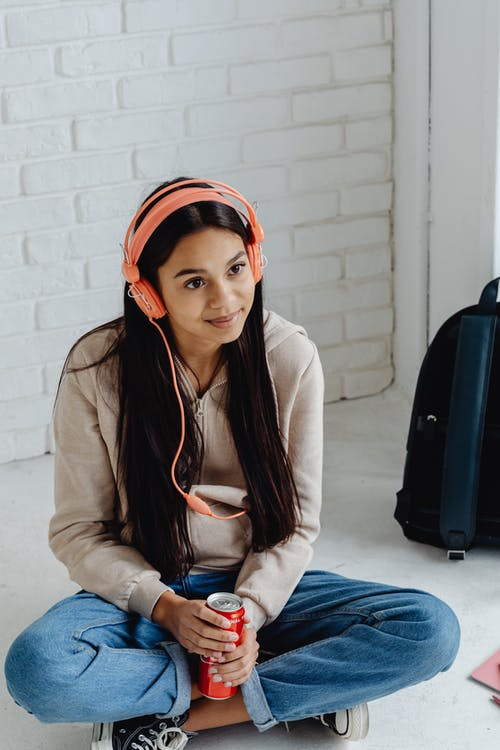 Smiling Teenager Sitting on the Floor while Listening to Music