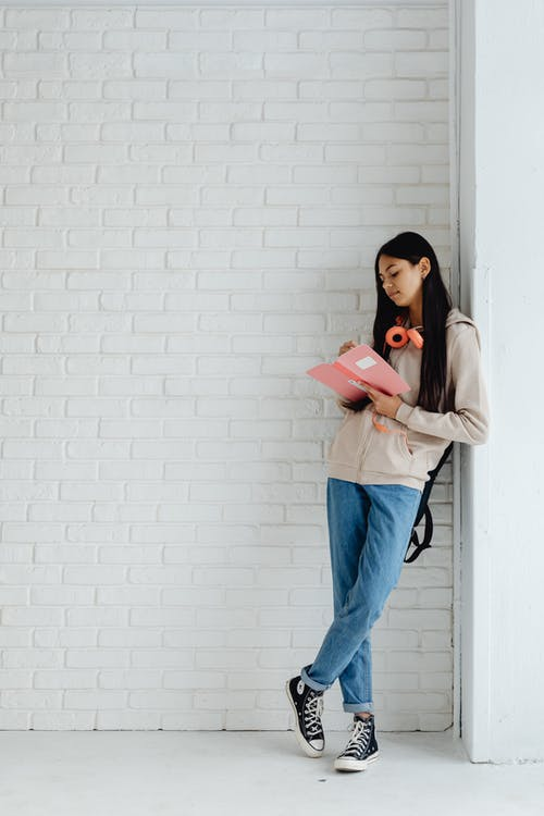 Female Teenager Writing on Her Notebook while Leaning on the Wall