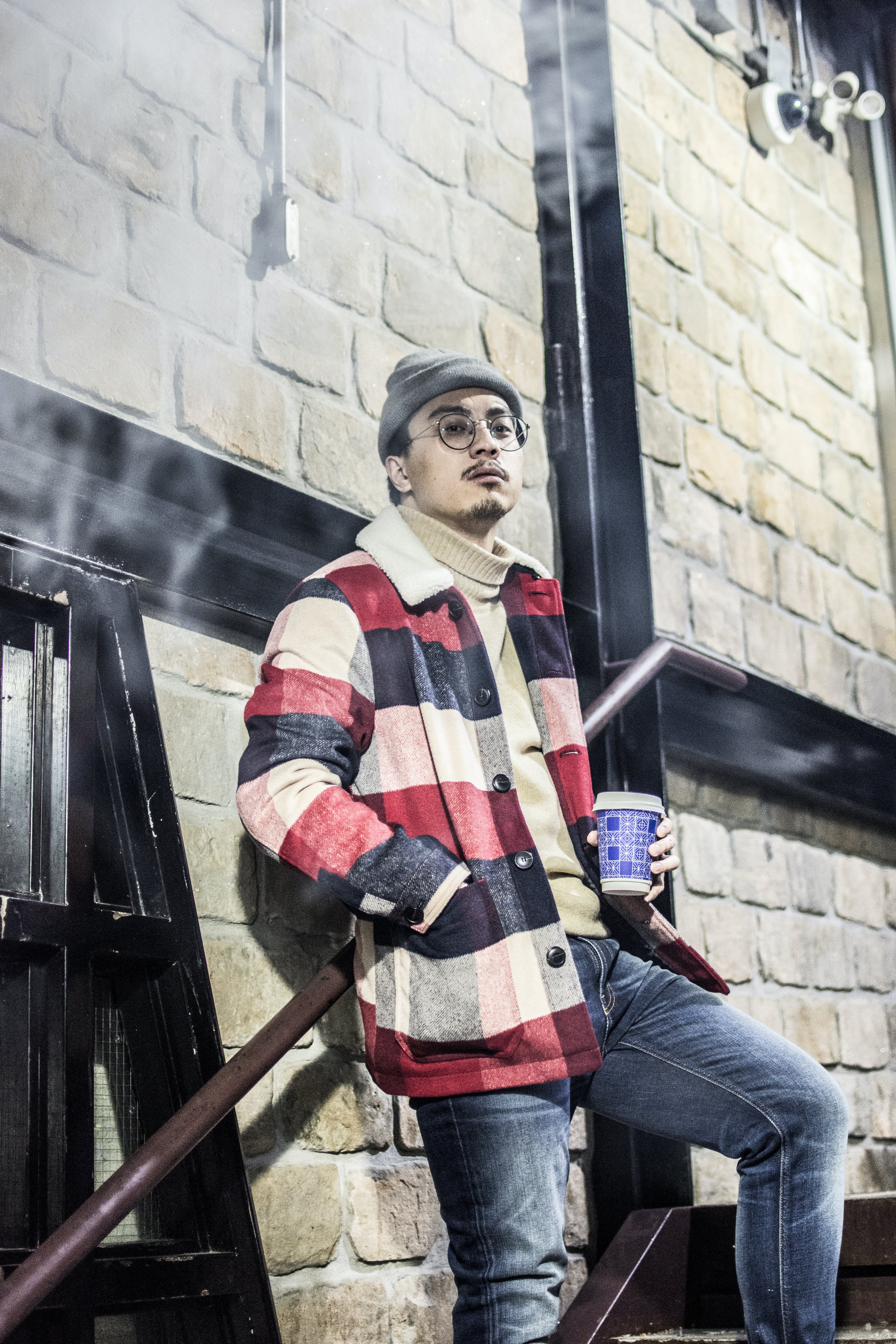 Man in Red, Black, and Grey Plaid Button-up Jacket With Blue Denim Jeans Outfit Holding Disposable Cup Stands Beside Brown Concrete Wall