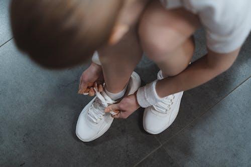 Безкоштовне стокове фото на тему «білі кросівки, взуття, зав'язує взуття»