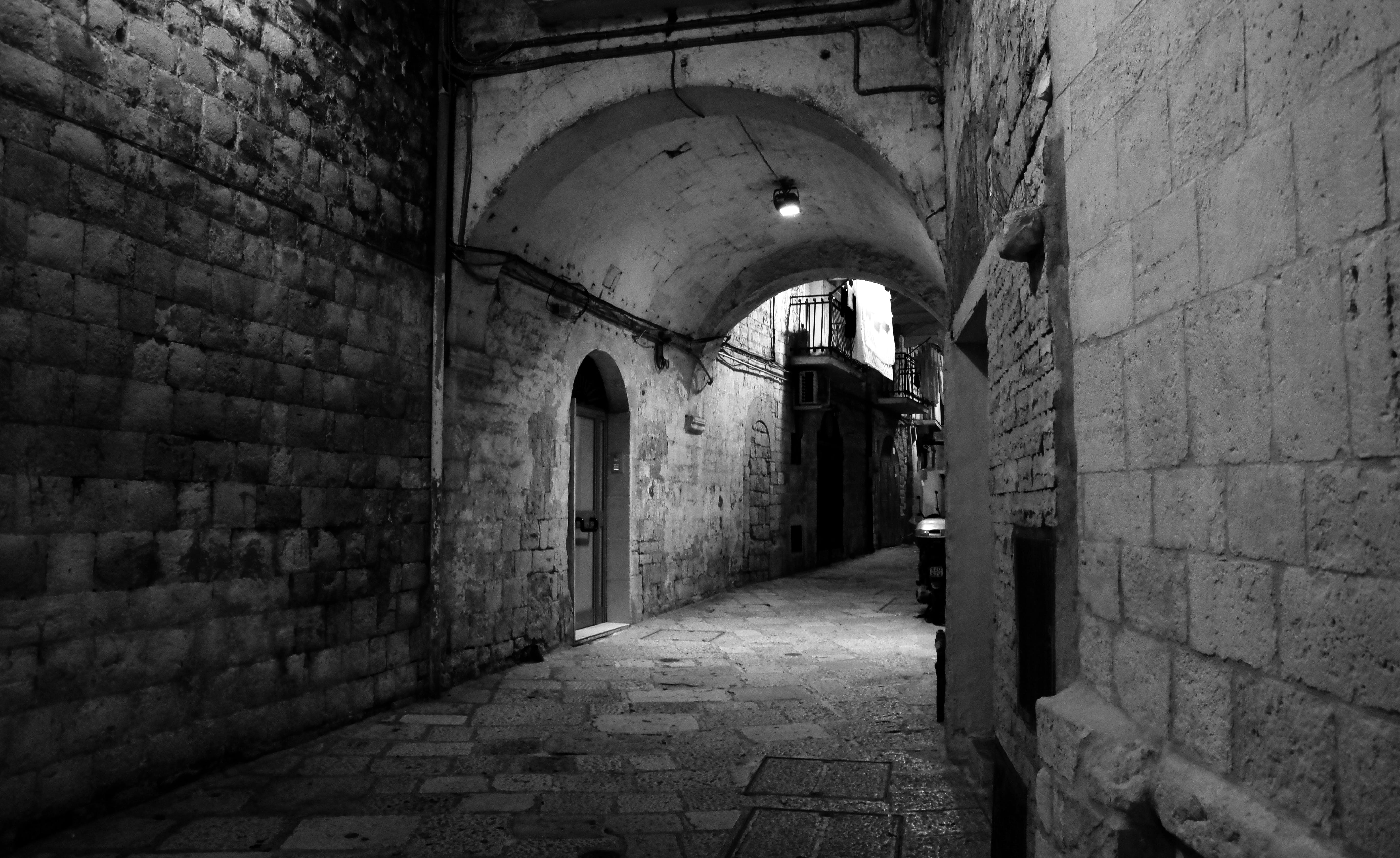 Grayscale Photo of Brick Walled Alley