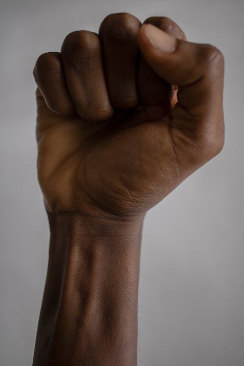 Crop black person raising fist
