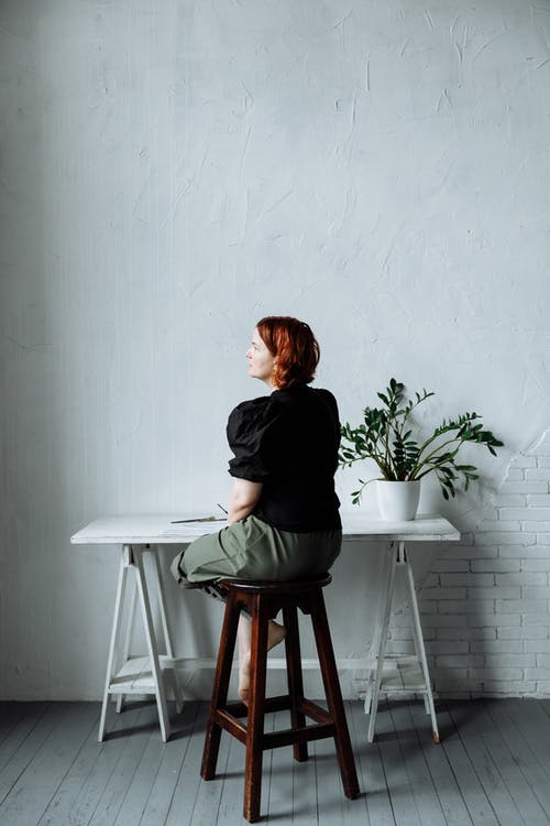 A Woman Sitting on a Bar Stool with a Distant Look