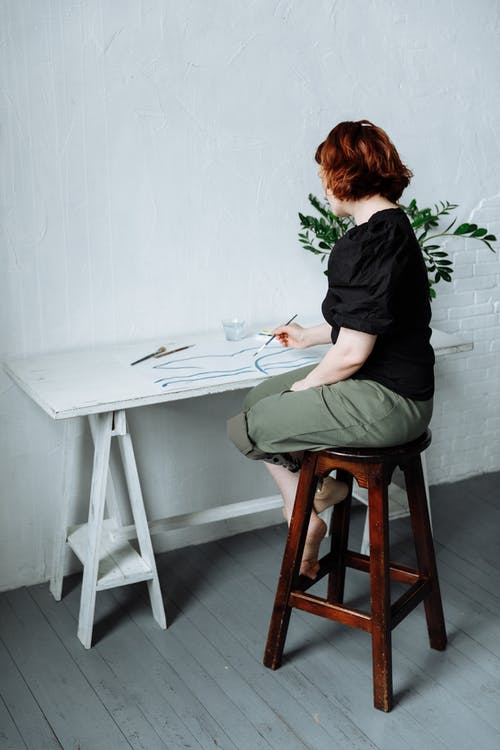 A Woman Painting on a Table