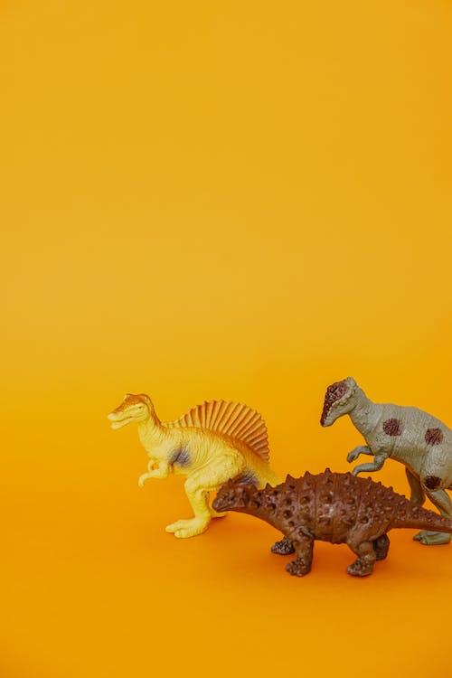 Miniature Dinosaurs in Orange Background