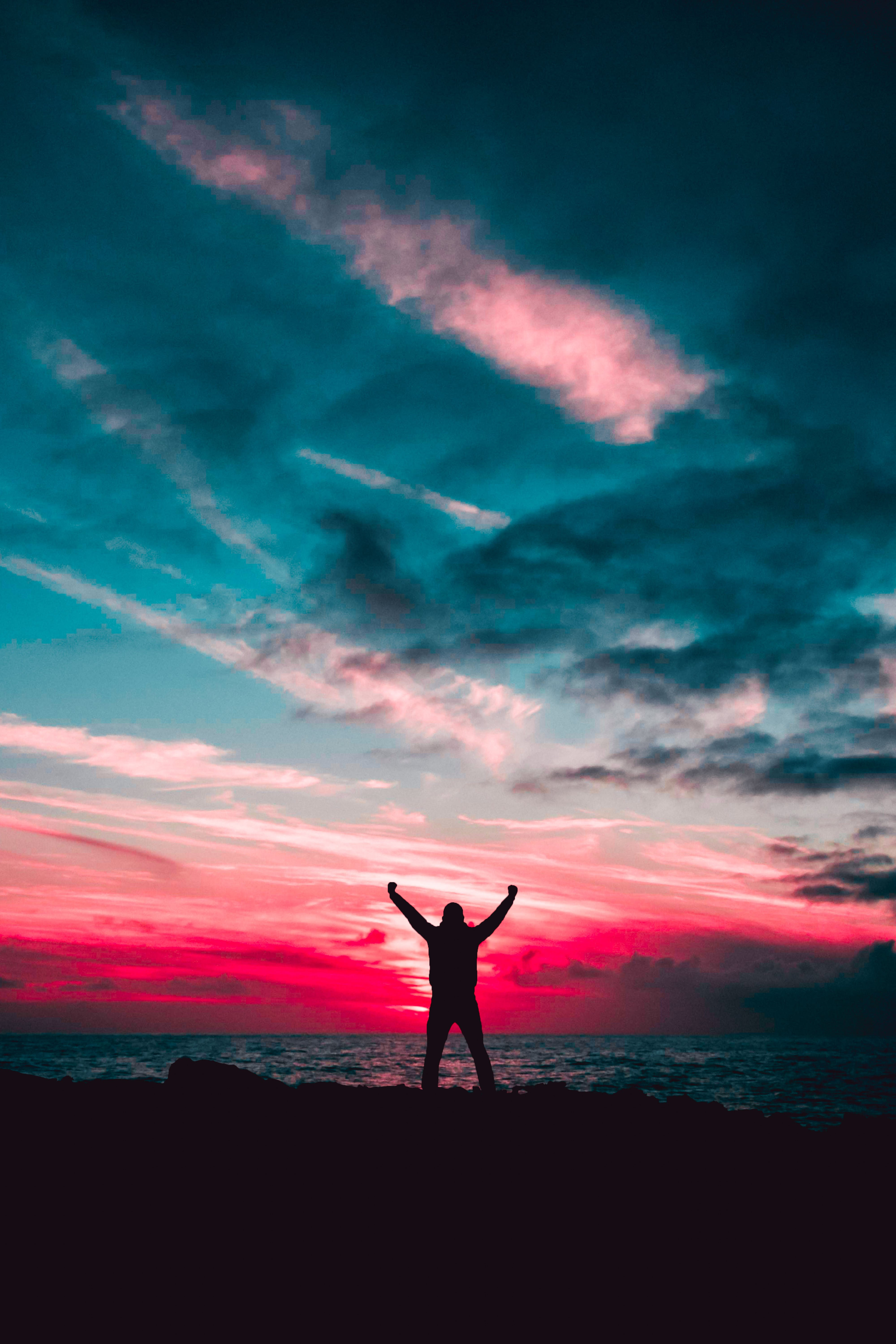 Silhouette of Man Raising Hands Against a Red Sunset Light Under Green Clouds