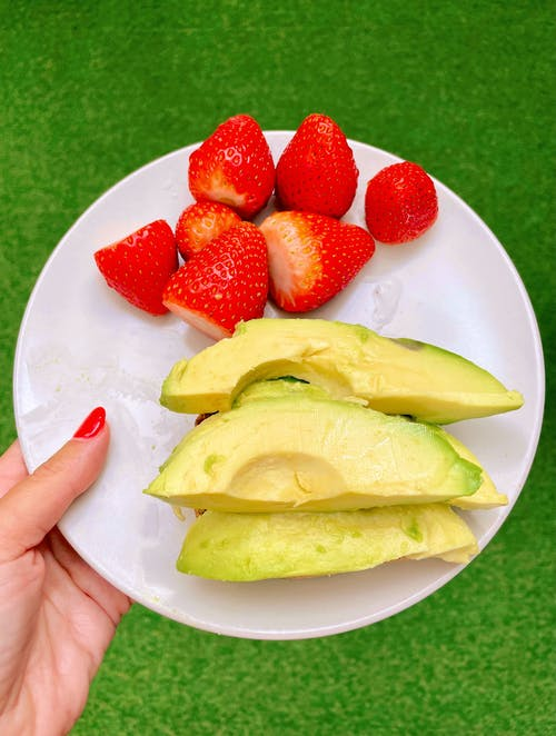 Close-Up Shot of a Person Holding a Plate with Slices of Avocados and Fresh Strawberries