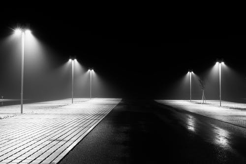 Grayscale Photo of Street Lights at Night