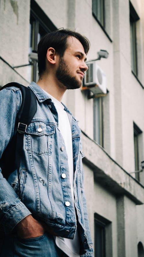 Man in Blue Denim Jacket Standing Near Building
