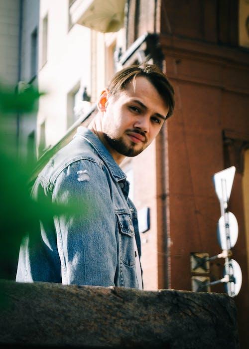 Man in Blue Denim Jacket Standing Near Green Wall