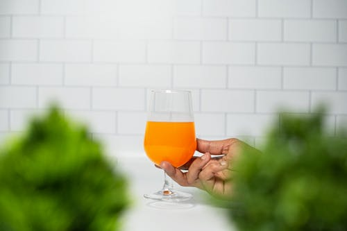 Person Holding Clear Wine Glass With Orange Liquid