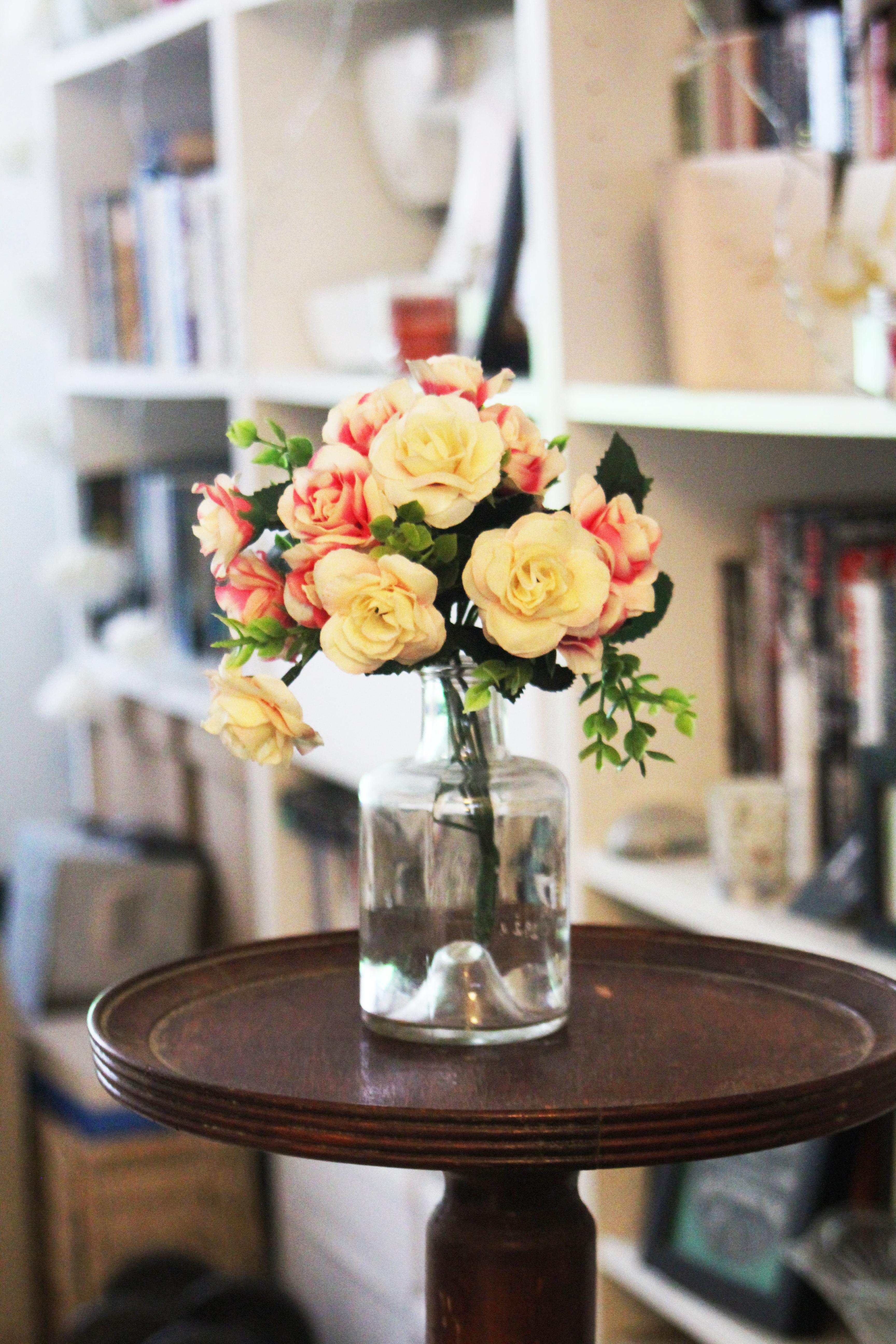 Arrange of Petal Flower in Clear Glass Vase at Table