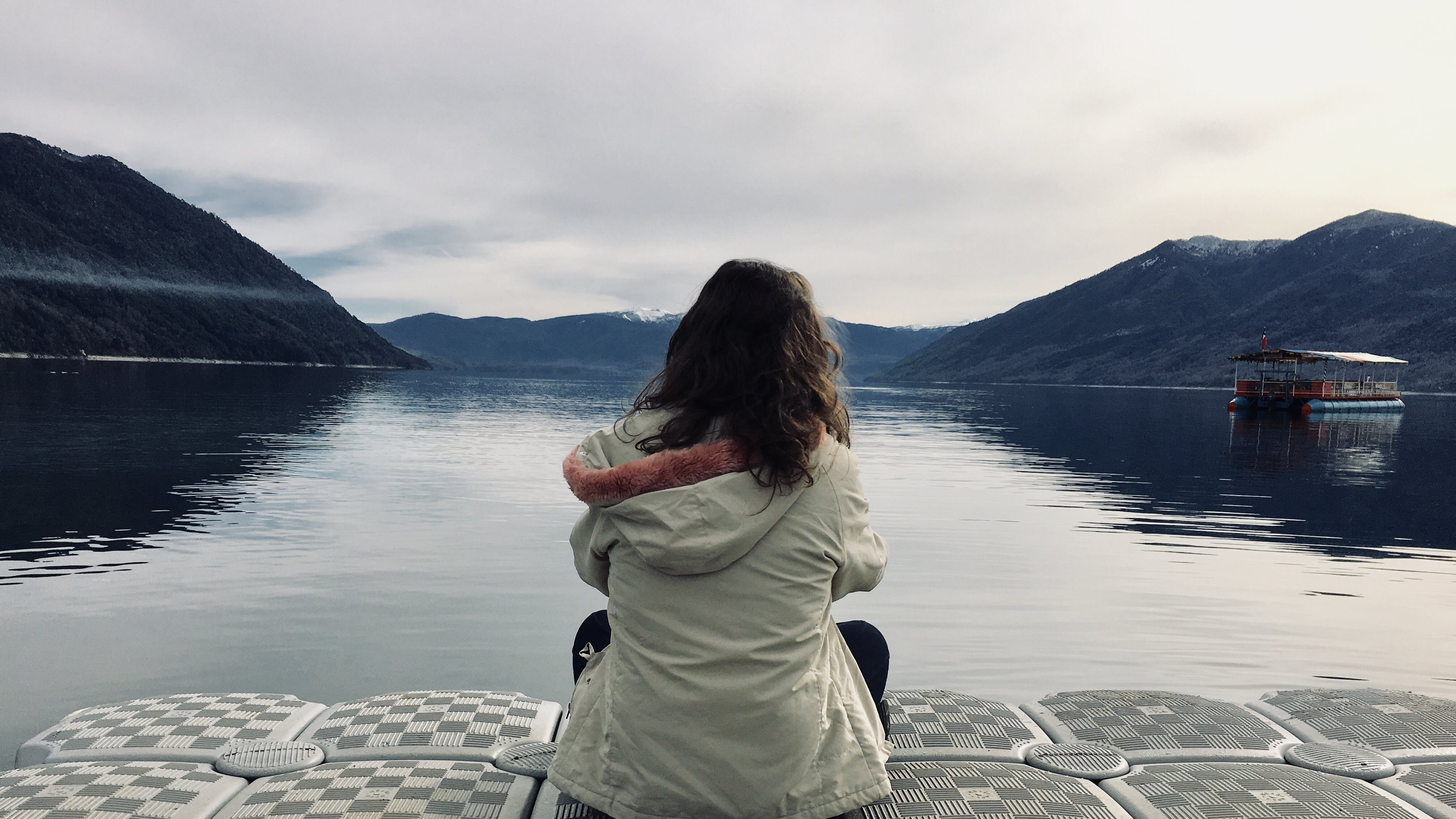 Woman Wearing Gray Jacket in Front of Body of Water