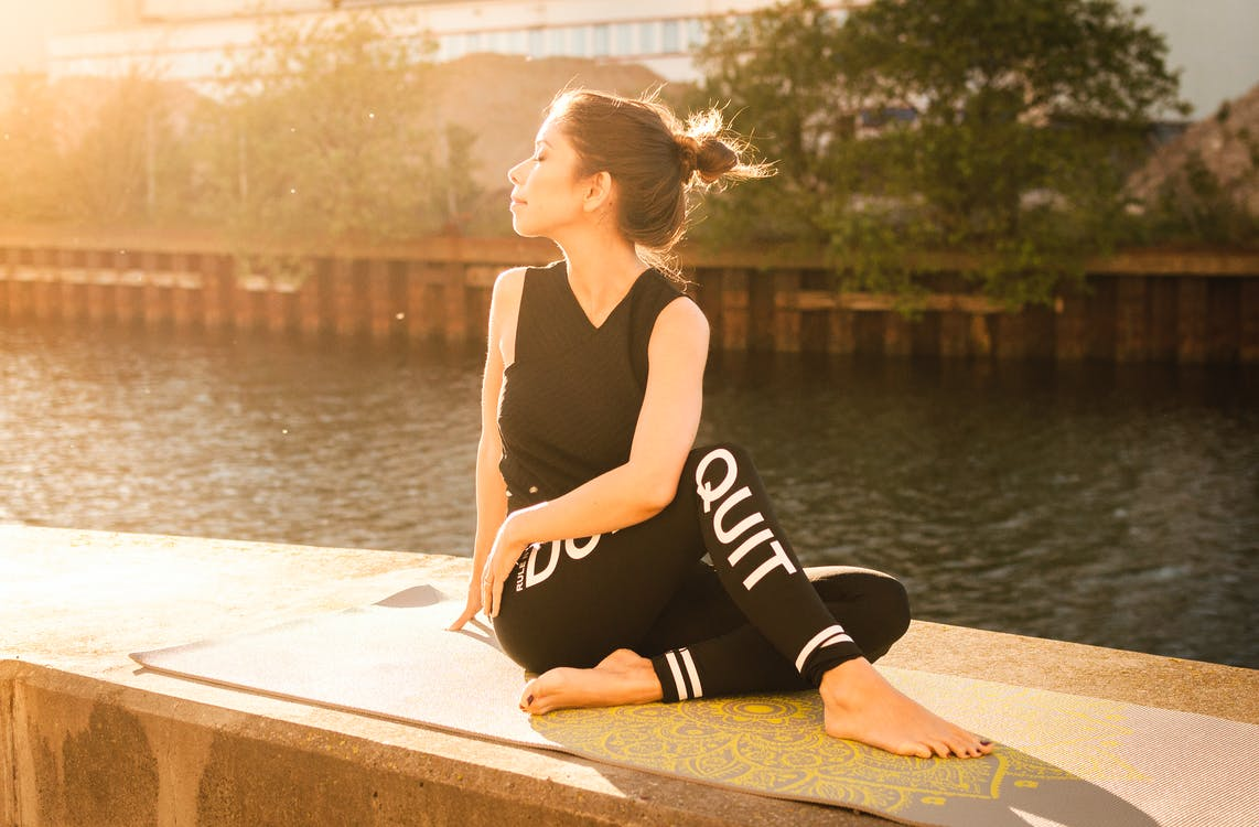 Woman Wearing Black Fitness Outfit Performs Yoga Near Body of Water