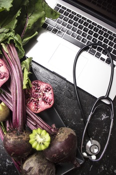 Macbook Pro With Stethoscope With Kiwi and Vegetables on Black Wooden Surface