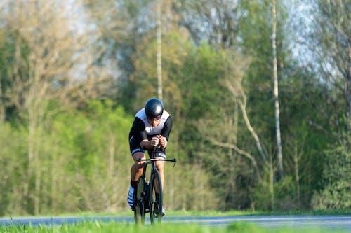 Man in Black Helmet Riding Bicycle