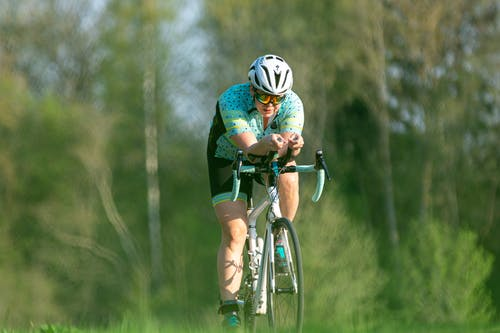 Person in Bicycle Helmet Riding on Green Bicycle