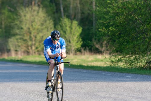 Man in Blue Shirt and Black Helmet Riding on Bicycle