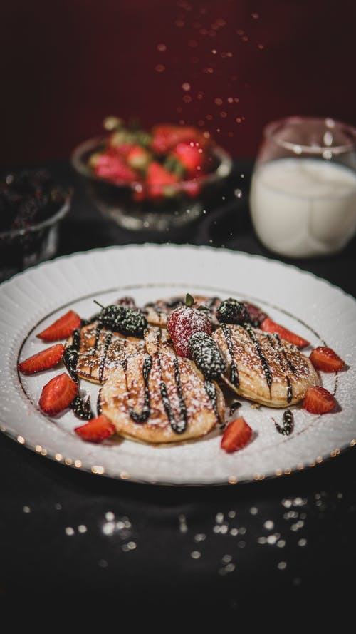 Pancakes with Powdered Sugar Dusting and Chocolate Syrup