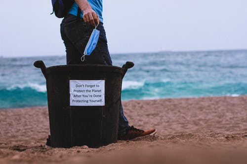 Person in Black Jacket Holding Blue Plastic Bag on Brown Sand Beach