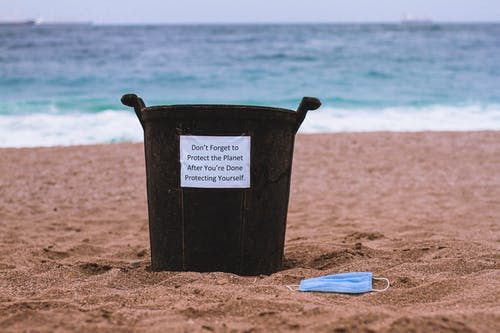 Black Plastic Bucket on Brown Sand Near Blue and White Plastic Pack