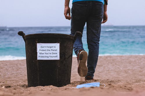 Person in Blue Denim Jeans and Brown Boots Standing on Beach Shore