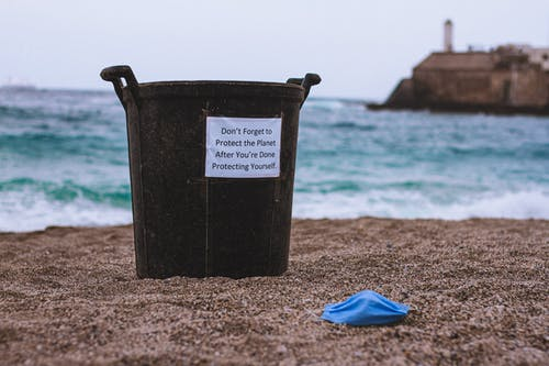 Black and White Plastic Bucket on Brown Sand Near Blue Textile