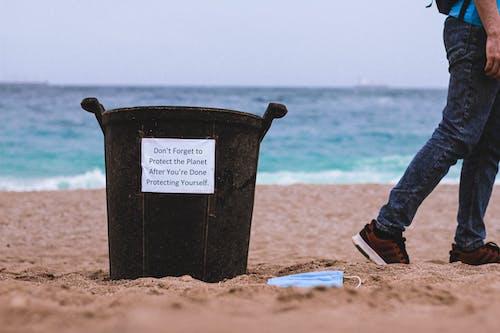 Black Plastic Bucket on Brown Sand Near Body of Water