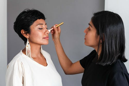 A Makeup Artist Applying Makeup on a Woman