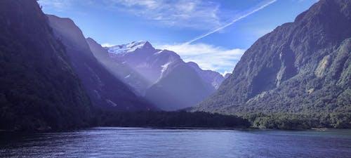 Body Of Water Near Mountain Under Clear Sky