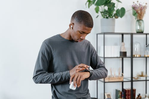 Man in Gray Sweater Using His Smartwatch