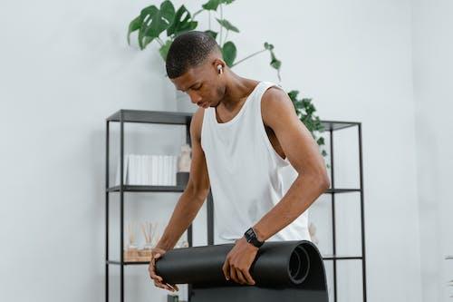 Man Holding a Black Yoga Mat