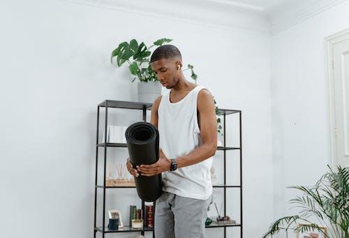 Man in White Tank Top Holding a Black Yoga Mat