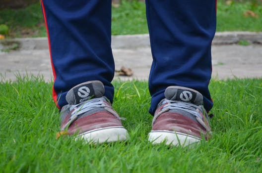 Person in Red Grey Sneakers on Green Grass