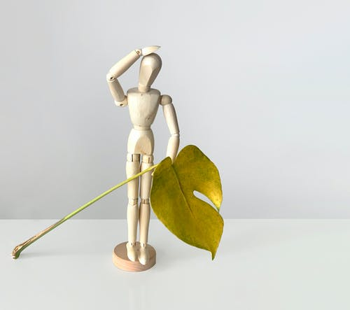 Gold Colored Figurine With Green Leaf