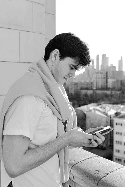 Grayscale Photo of a Man Using a Cellphone