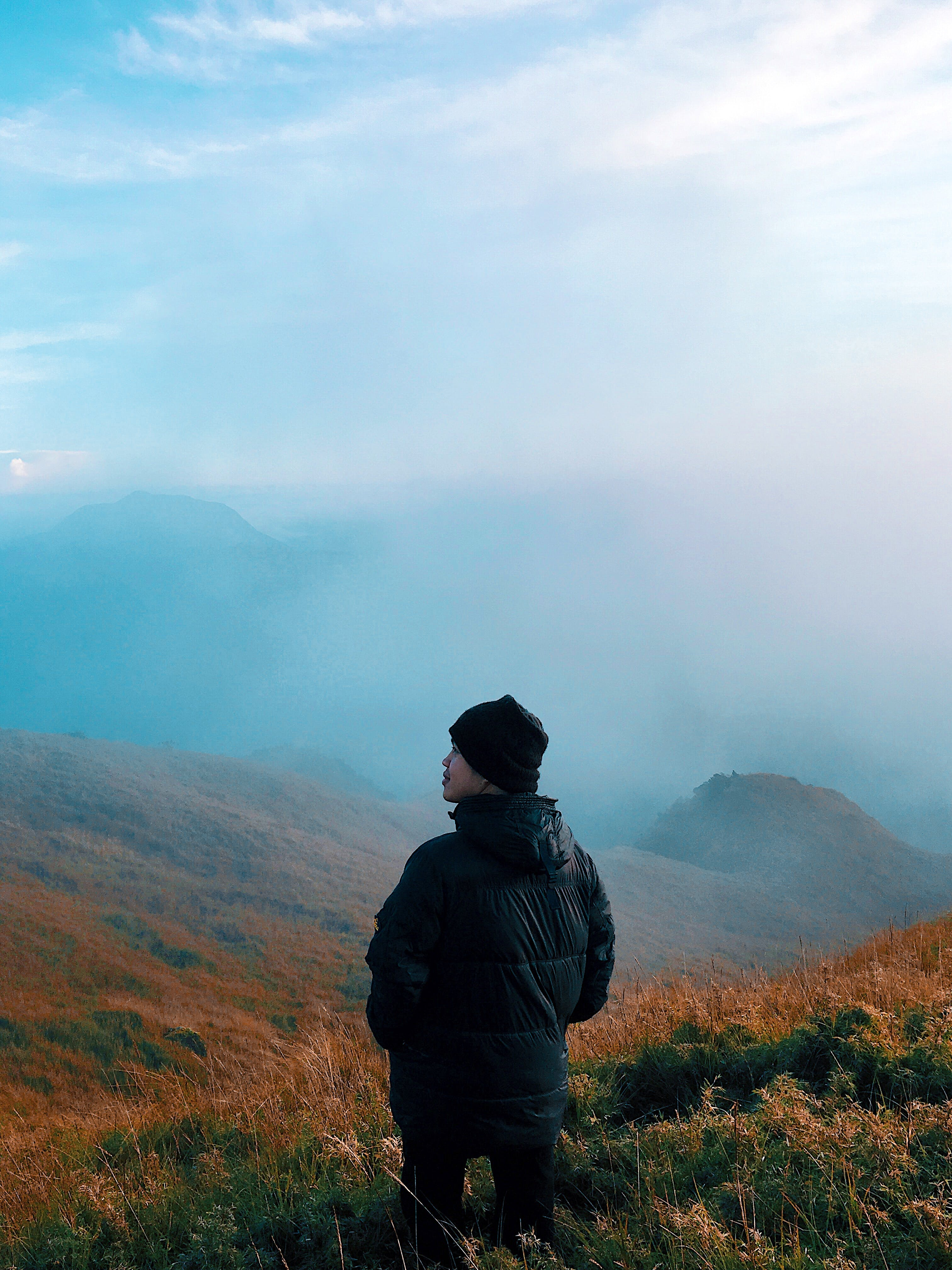 Man in Black Jacket Standing on Mountain With Fog