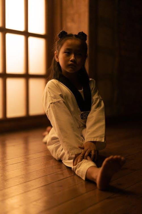 Girl in White Jacket Sitting on Floor