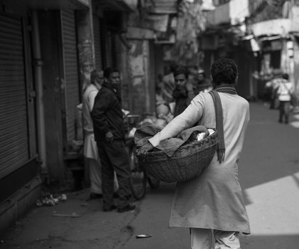 Grayscale Photo of Woman Carrying Basket
