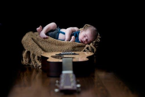 Foto d'estoc gratuïta de bebè, desenfocament, fons negre, guitarra