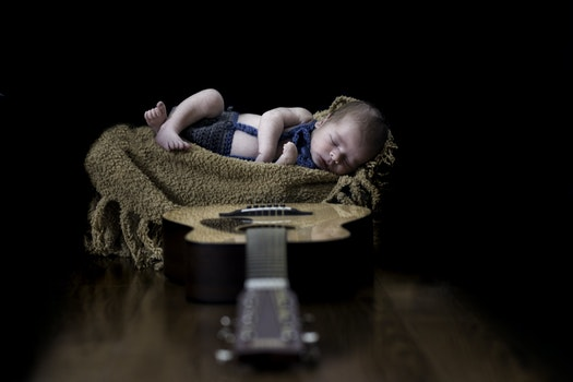 Baby on Beige Textile Near Brown Dreadnought Acoustic Guitar