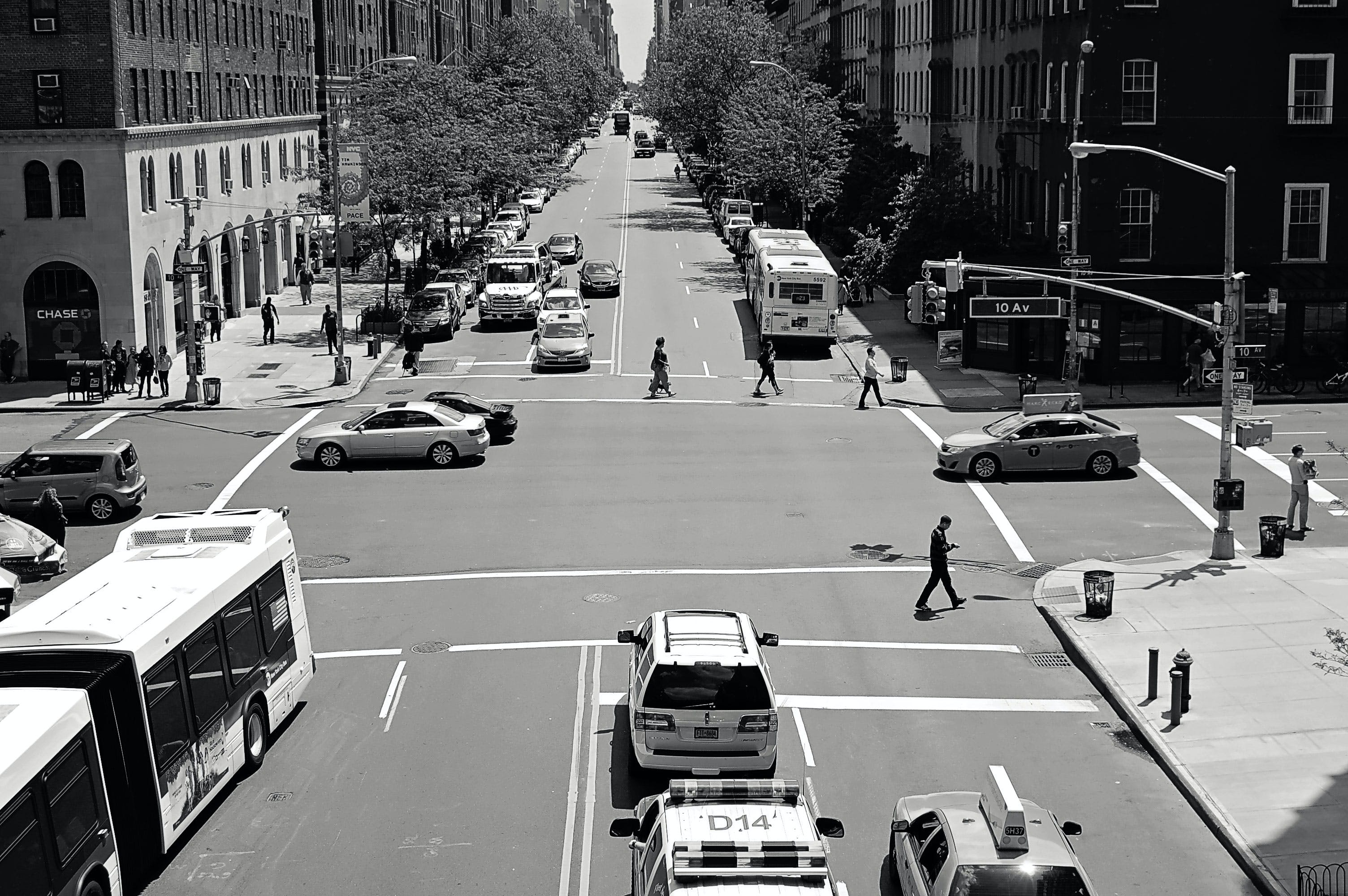 Greyscale Photo of Car and People on Streets