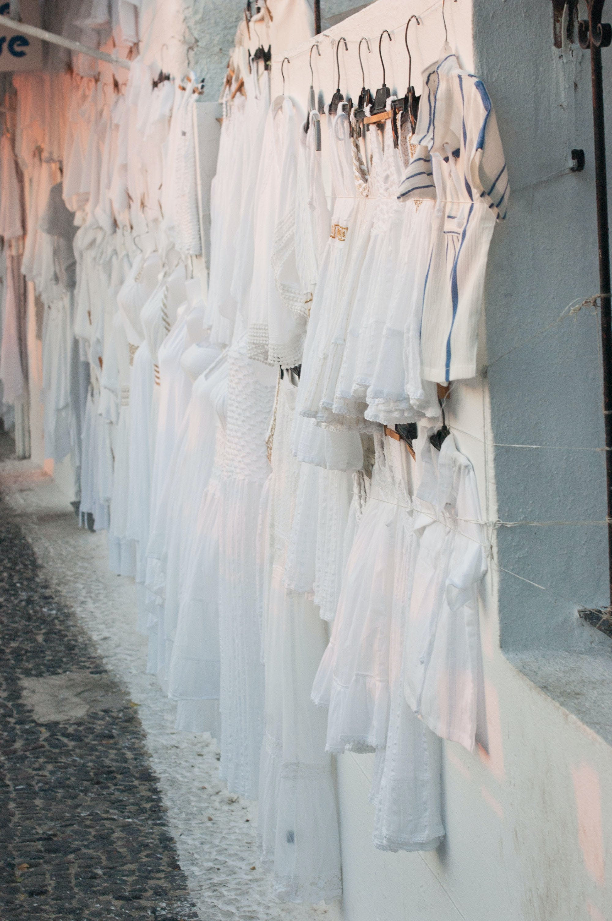 Assorted Dresses Hanged on White Painted Wall